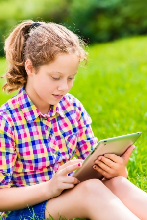 Closeup outdoor portrait of a pretty  teenager girl in casual clothes sitting on the grass in sunlight with digital tablet in her hands Stok Fotoğraf