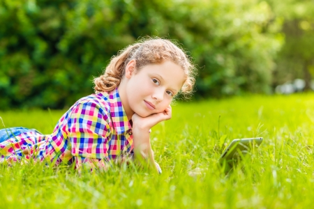 Pretty teenager girl in casual clothes lying on the grass in sunlight with digital tablet or e-book, outdoor portrait