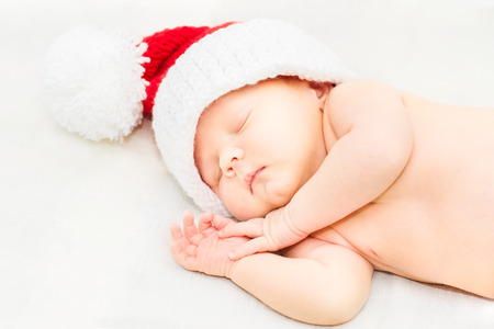 Adorable sleeping newborn baby wearing Santa Claus hat, Christmas, New Year Stock Photo