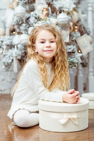Lovely blond little girl sitting under the Christmas tree with gift box photo