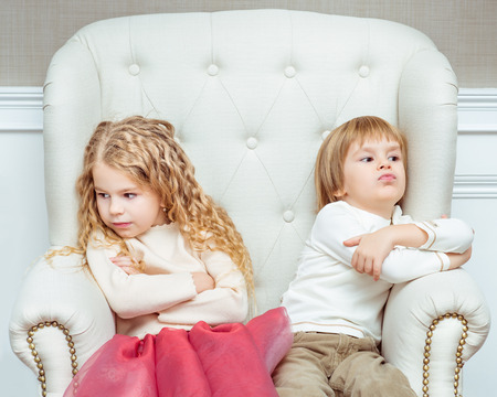 Cute little siblings (boy and girl) being at odds with each other, sitting on armchair
