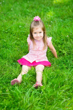 six girls: Cute little girl with long blond hair in pink blouse and skirt sitting on grass in summer park, outdoor portrait Stock Photo