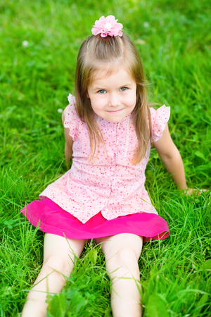 5 6 years: Beautiful little girl with long blond hair, sitting on grass in summer park, outdoor portrait Stock Photo