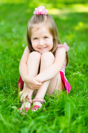 Cute little girl with long blond hair, sitting on grass in summer park putting her hands around her legs, outdoor portrait Stock Photo