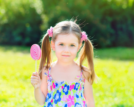 Adorable little girl with two blond ponytails holding white and pink lollipop in her hand, outdoor summer portrait Stock Photo - 26656867