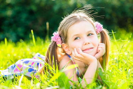 5 6 years: Cute smiling little girl with two blond ponytails laying on grass in summer park, outdoor portrait