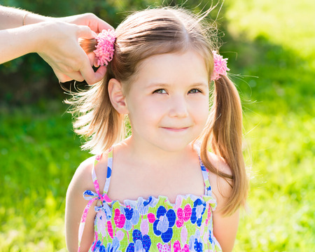 scrunchie: Sweet smiling little girl with her moms hands making hairstyle (ponytail), outdoor closeup portrait in summer park Stock Photo