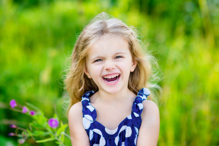Fanny and beautiful laughing little girl with long blond curly hair, outdoor portrait in summer park on bright sunny day. Child in green grass field with purple flowers. Closeup portrait.