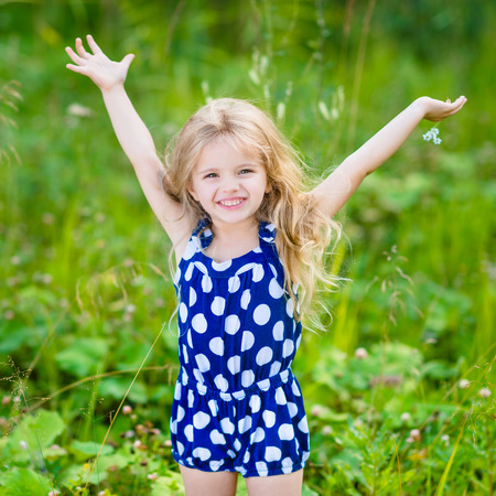 Cute smiling little girl with long blond curly hair and flower in her hands. Girl with raised hands. Outdoor full-length portrait in summer park on bright sunny day. Child in green grass field.