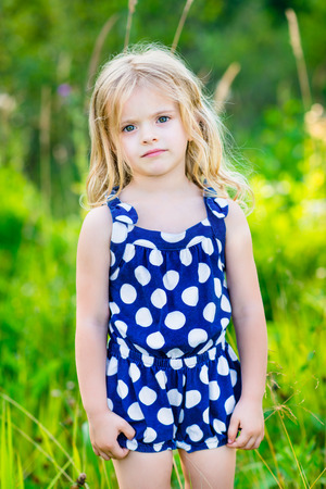 rompers: Cute little girl with long blond curly hair, outdoor full length portrait in summer park on bright sunny day. Pensive child in green grass field. Calmness and tenderness.