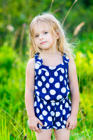 rompers: Sweet little girl with long blond curly hair, outdoor full length portrait in summer park on bright sunny day. Thoughtful child in green grass field. Calmness and tenderness. Stock Photo