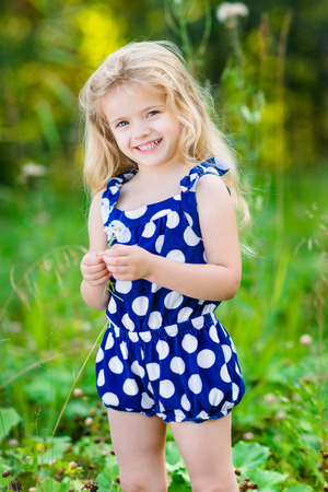 pose: Beautiful smiling little girl with long blond curly hair and flower in her hands. Outdoor full-length portrait in summer park on bright sunny day. Child in green grass field. Stock Photo