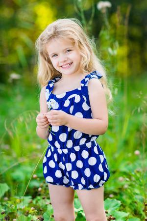 ni�os rubios: Hermosa ni�a sonriente con el pelo largo y rubio y rizado y flor en sus manos. Al aire libre retrato de cuerpo entero en el parque de verano en un d�a soleado brillante. Ni�o en campo de hierba verde.