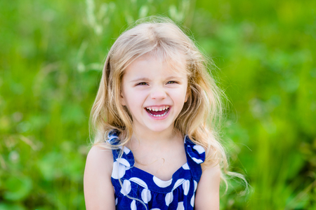 Pretty laughing little girl with long blond curly hair, outdoor portrait in summer park on bright sunny day. Smiling child in green grass field with purple flowers. Closeup portrait.