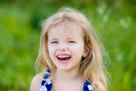 Adorable laughing little girl with long blond curly hair, outdoor portrait in summer park on bright sunny day. Smiling child in green grass field. Closeup portrait. photo