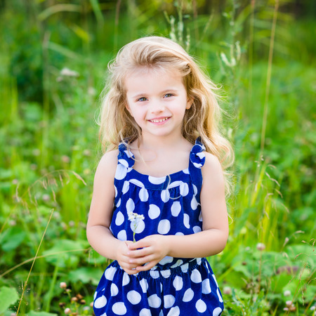 Beautiful smiling little girl with long blond curly hair and flower in her hands. Outdoor portrait in summer park on bright sunny day. Child in green grass field.