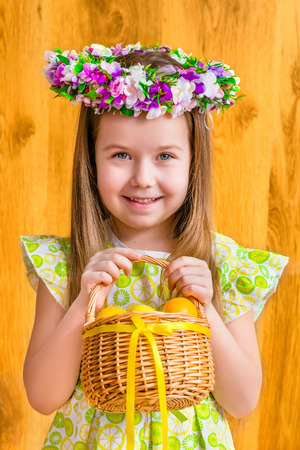 Portrait of adorable smiling little girl with long blond hair wearing floral head wreath and holding wicker basket with yellow eggs and ribbon. Easter celebrations. Wooden background. Studio portrait