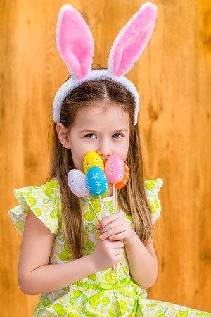 Portrait of smiling little girl with long blond hair wearing pink and white rabbit or bunny ears and holding bunch of painted colorful eggs. Easter celebrations. Wooden background. Studio portrait
