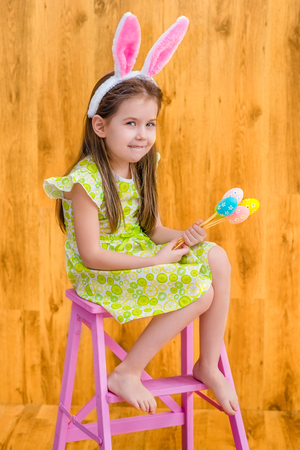 Barefooted little girl with long blond hair wearing pink white rabbit or bunny ears and holding bunch of colorful eggs sitting on pink chair. Easter celebrations. Wooden background. Studio portrait Фото со стока