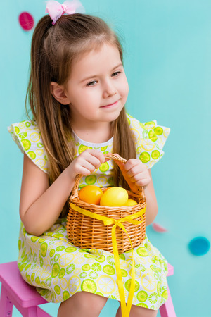 Thoughtful little girl with long blond hair wearing pink bow and holding wicker basket with yellow eggs and ribbon sitting on pink chair. Easter celebrations. Turquoise background. Studio portrait Фото со стока