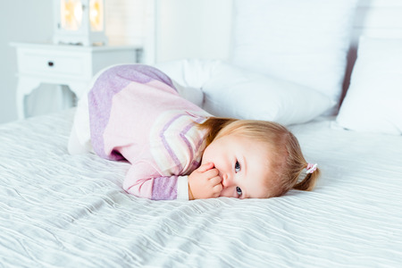 Cute little blonde girl on hands and knees on white bed in bedroom. White interior, big bed, bedside table and night lamp