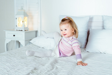 Funny and cute blond little smiling girl playing on bed in bedroom. White interior, big bed, bedside table and night lamp.