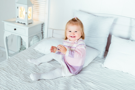 Funny and cute blond little laughing girl playing on bed in bedroom. White interior, big bed, bedside table and night lamp