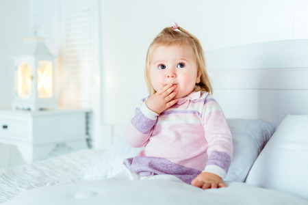 Funny surprised blond little girl sitting on bed in bedroom. White interior, big bed, bedside table and night lamp. Girl touches her mouth by hand