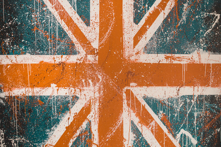 Painted concrete wall with faded graffiti of British flag. Grunge and vintage flag of United Kingdom. Union Jack Фото со стока