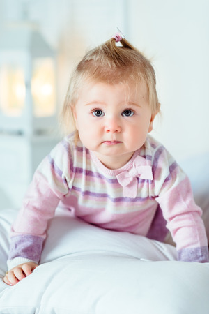 Sweet blond little girl with big grey eyes and plump cheeks staying on hands and knees on white bed in bedroom. White interior, bed, night lamp