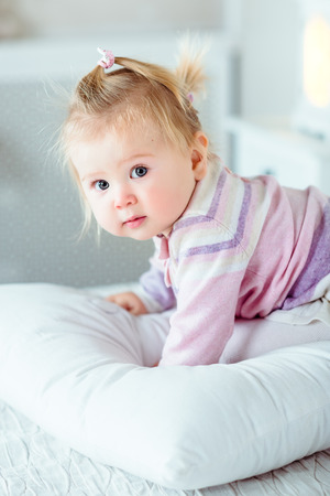 Adorable blond little girl with big grey eyes and plump cheeks staying on hands and knees on white bed in bedroom. White interior, bed, pillow, night lamp Stok Fotoğraf