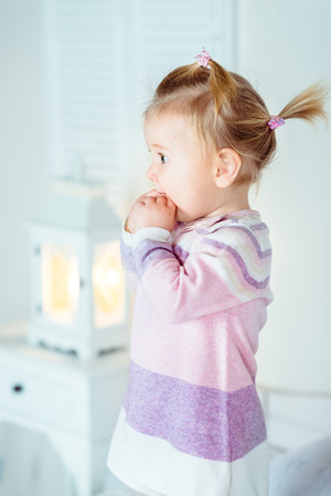 Amazed blond little girl with ponytail staying on bed and keeping her hands in her mouth. White interior, bedroom, night lamp