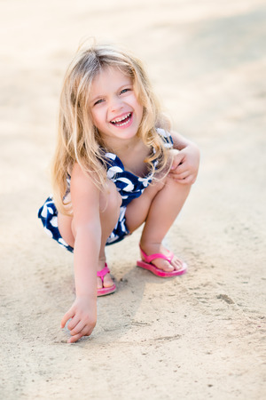 Beautiful laughing little girl with long blond hair  squatting and drawing in the sand on the beach in summer day Banque d'images