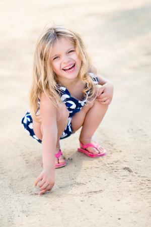 ni�os rubios: Hermosa ni�a de risa con largo pelo rubio en cuclillas y dibujo en la arena de la playa en d�a de verano