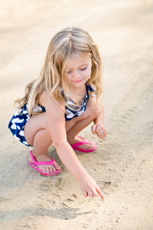 Sweet smiling little girl with long blond hair squatting and drawing in the sand on the beach in summer day photo