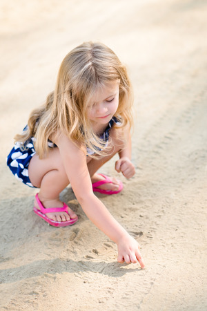 Cute thoughtful little girl with long blond hair squatting and drawing in the sand on the beach in summer day