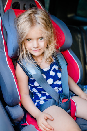Adorable smiling little girl with long blond hair buckled in car seat looking through the car window 스톡 콘텐츠