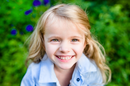 Close-up portrait of a smiling blond little girl wearing a blue jacket in sunny summer day