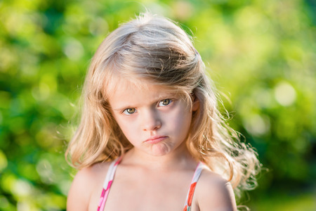wretched: Close-up portrait of sad blond little girl with pursed lips. Sunny summer day in beautiful park Stock Photo