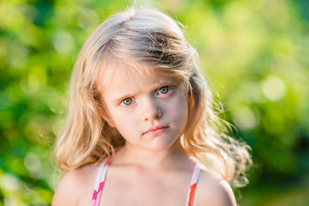 unworried: Close-up portrait of thoughtful little girl with long blond hair. Sunny summer day in beautiful park
