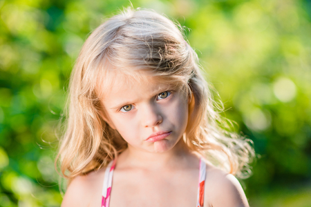 wretched: Close-up portrait of displeased blond little girl with pursed lips. Sunny summer day in beautiful park