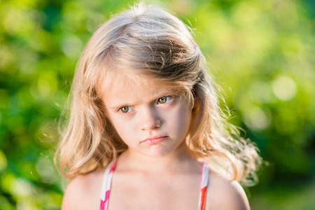 doleful: Close-up portrait of capricious blond little girl with pursed lips. Sunny summer day in beautiful park
