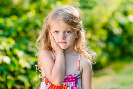 Sad little girl with long blond hair suffering from toothache. Sunny summer day in beautiful green park Фото со стока