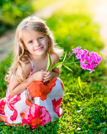 Smiling pretty little girl squatting and holding purple flower in sunny summer day in beautiful park