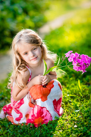 girl squatting: Thoughtful pretty little girl squatting and holding purple flower in sunny summer day in beautiful park Stock Photo