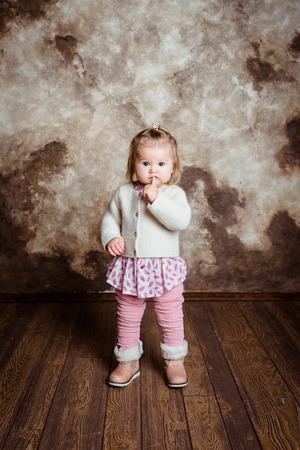 Cute blond little girl with big grey eyes and plump cheeks staying and keeping her finger in her mouth. Studio portrait on grunge background