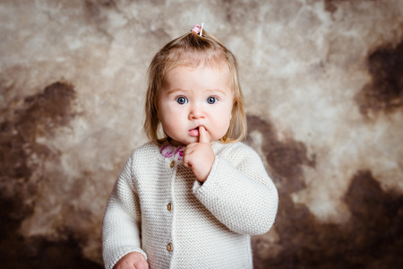 Close-up portrait of cute blond little girl with big grey eyes and plump cheeks keeping her finger in her mouth. Studio portrait on grunge background