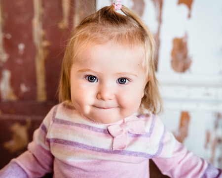 Close-up portrait of funny blond little girl with big grey eyes and plump cheeks with pursed lips. Studio portrait on grunge background