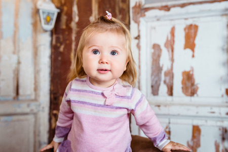 Amazed funny blond little girl with big grey eyes and plump cheeks looks up. Studio portrait on grunge background