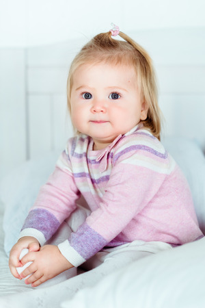Cute blond little girl with big grey eyes and plump cheeks sitting on bed in bedroom and holding her leg with her hands Фото со стока